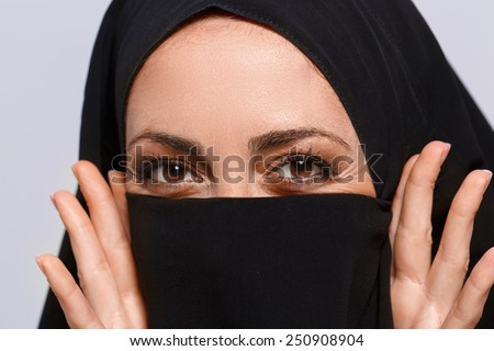 Her beauty lies in her eyes. Closeup image of beautiful young Muslim woman in chador covering her face with  dark cloth and smiling at camera isolated on grey background - stock photo