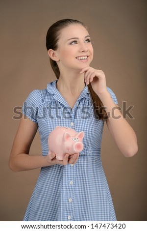 Her first savings. Pretty teenage girl holding a piggy bank and smiling away while isolated on brown - stock photo