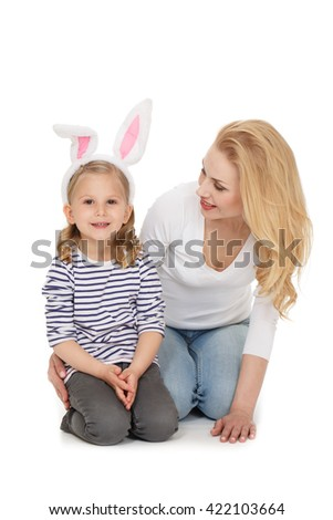 Her little cutie. Portrait of a beautiful woman looking at her little daughter wearing bunny ears smiling happily at the studio on white background. - stock photo