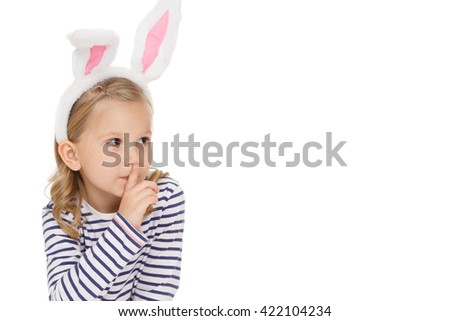 Her little secret. Studio shot of a gorgeous little girl making shushing gesture looking at the copyspace on the side isolated on white. - stock photo