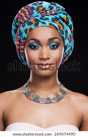 Her perfection in her style. Beautiful African woman wearing headscarf and necklace looking at camera while standing against black background - stock photo
