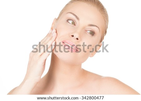 Her silky smooth skin. Closeup studio portrait of a gorgeous happy woman applying moisturizer to her face