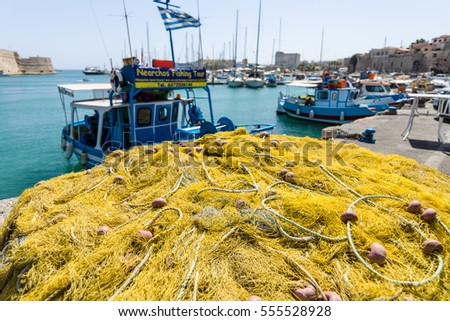 HERAKLION, GREECE - JULY 16, 2016: Crete. Fishing nets on the quayside. Moored fishing boats in the background.