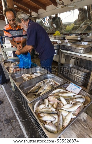 HERAKLION, GREECE - JULY 16, 2016: Crete. The buyer and the seller. Fish market in Heraklion, near the seaport.