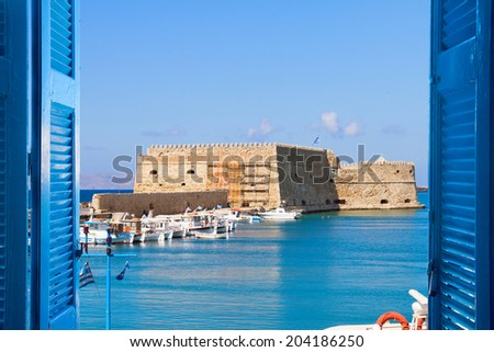 Heraklion harbour with old venetian fort through window sills, Crete, Greece - stock photo