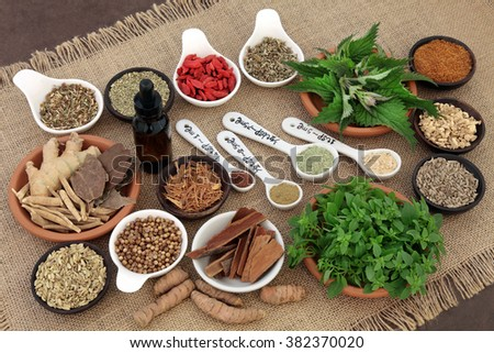 Herb and spice and health food selection in porcelain bowls over hessian background. Used in natural alternative herbal medicine for men. Selective focus. - stock photo