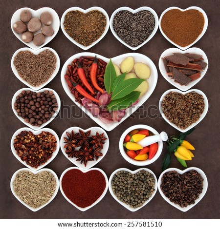 Herb and spice ingredients in a heart shaped porcelain dishes and mortar with pestle. - stock photo
