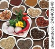 Herb and spice ingredients in a heart shaped porcelain dishes over old oak background. - stock photo