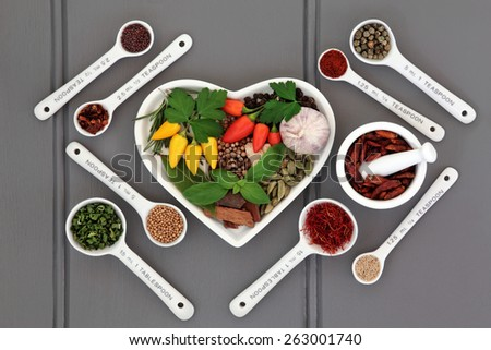 Herb and spice ingredients with measuring spoons and mortar with pestle over wooden grey background. - stock photo
