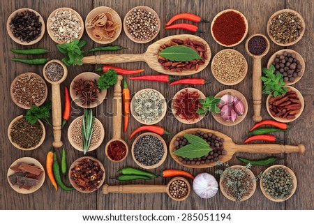 Herb and spice selection in wooden bowls, spoons and  loose over old oak background. - stock photo