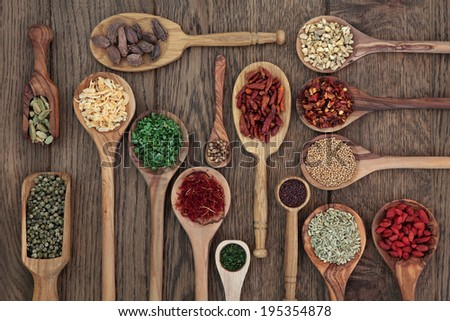 Herb and spice selection in wooden spoons and scoops over oak wood background. - stock photo