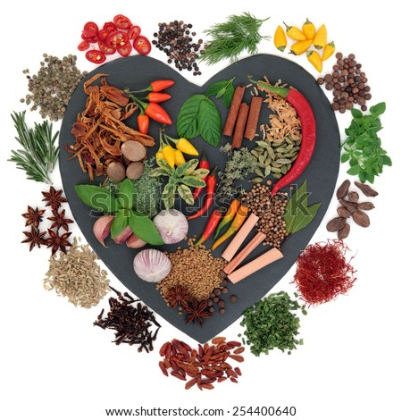Herb and spice selection on heart shaped slate over white background. - stock photo