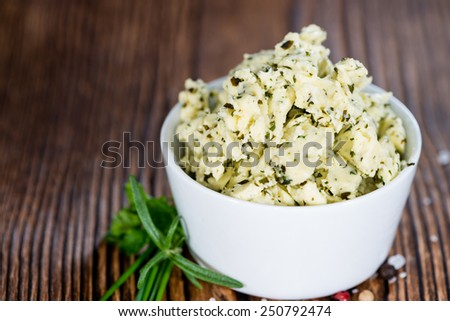 Herb Butter (close-up shot) in a bowl on wooden background