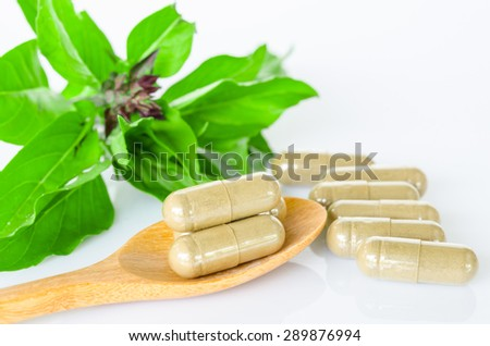 Herb capsule medicine in wooden spoon and green leaf on white background. - stock photo