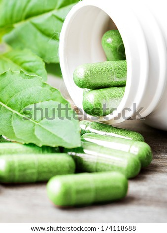 Herb capsule spilling out of a bottle - stock photo