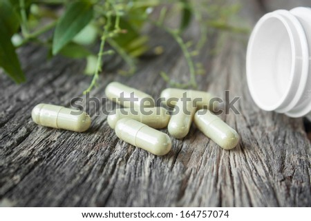 Herb capsule with green herbal leaf and bottle - stock photo