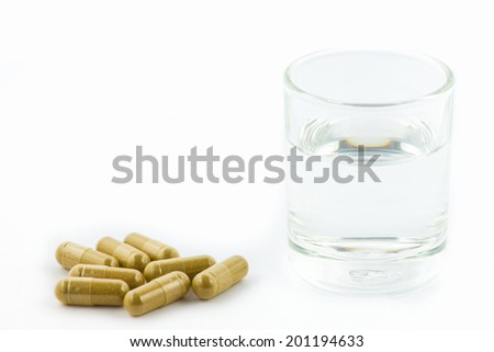 Herbal capsules and glass of water on white