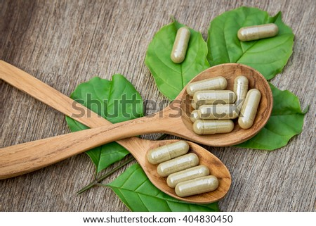 Herbal capsules on wooden spoon. herbs for healthy life.  - stock photo
