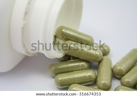 herbal capsules spilling out of a bottle