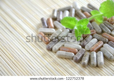 herbal capsules with mint leaves - stock photo