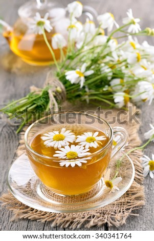 Herbal chamomile tea in glass cup on wooden table - stock photo