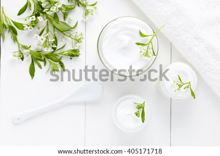 Herbal dermatology cosmetic hygienic cream with flowers skincare product in glass jar on white background - stock photo