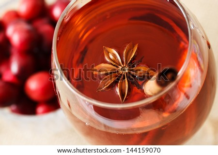 Herbal drink with star anise, a cinnamon stick and cranberries