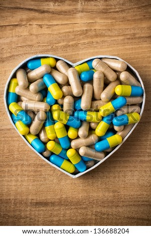 Herbal drug capsules, a heart-shaped box. Wooden surface. Alternative medicine concept. - stock photo