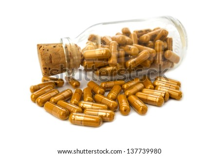 Herbal drug capsules in glass bottle on white background - stock photo