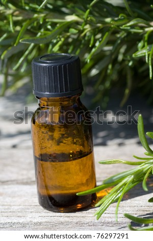 Herbal essence in a dropper bottle with fresh rosemary