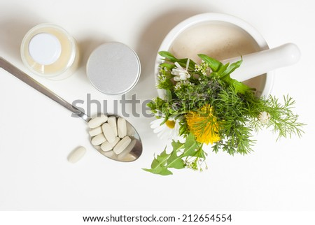 herbal flowers in mortar and modern medicines - stock photo
