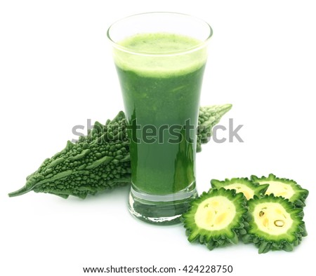 Herbal juice of green momodica in a glass with sliced vegetables
