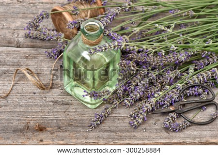 Herbal lavender oil with fresh flowers bouquet on wooden background. Vintage style still life - stock photo