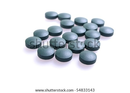 herbal laxative green coloured pill over white - stock photo