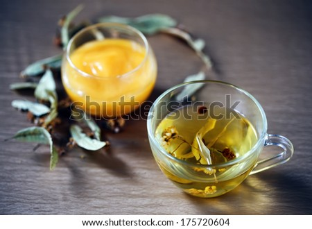 herbal linden tea in glass cup, honey and dry flowers on tablecloth