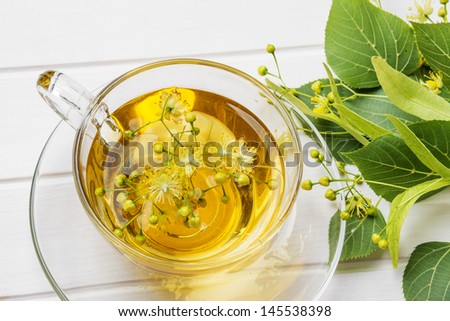herbal linden tea on a white wooden table - stock photo