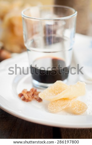 Herbal Liqueur with Crystallized Ginger and Brown Rock Sugar on a White Plate, shallow dof - stock photo