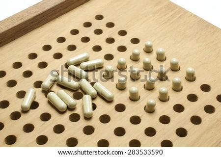 Herbal medicine capsules and capsule filling machine made of wood. - stock photo