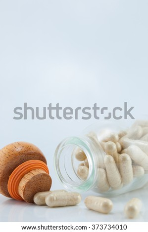 Herbal medicine capsules in a glass bottle - stock photo