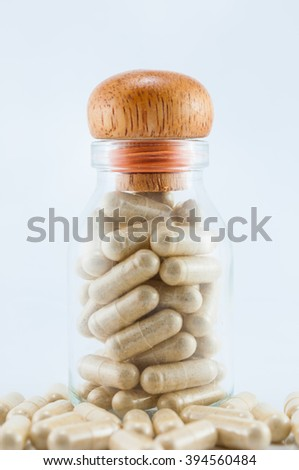 Herbal medicine capsules in a glass bottle