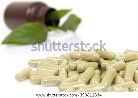 Herbal medicine capsules on white background. - stock photo