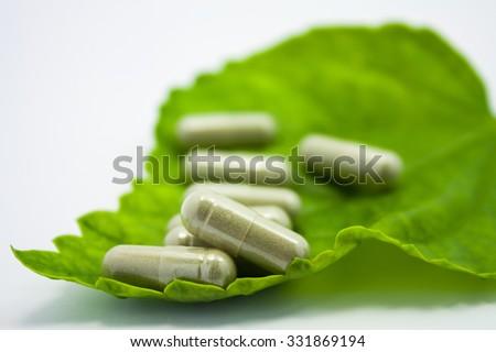 herbal medicine capsules pills on green organic herb leaf - stock photo