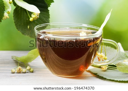Herbal medicine: cup with linden tea and flowers on wooden table - stock photo
