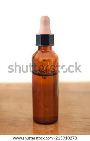 Herbal medicine or aromatherapy dropper bottle on wood