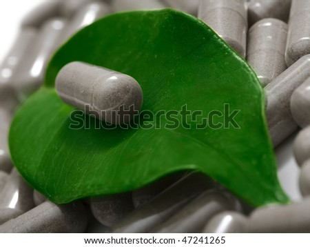 herbal medicine - pill on green leaf over film of pills