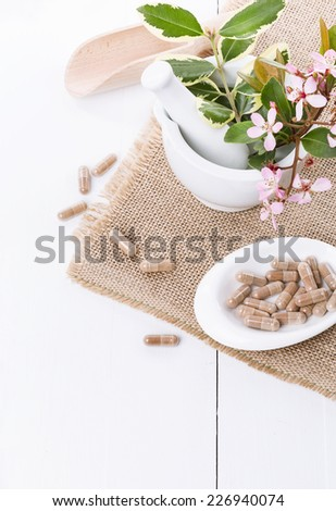 Herbal medicine pills and mortar on a burlap cloth over white background - stock photo