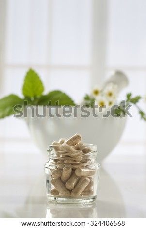 Herbal medicine pills and mortar over bright  background - stock photo