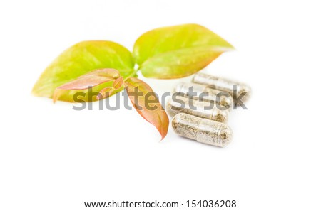 herbal medicine pills with green plant on white background - stock photo