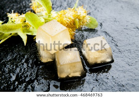 Herbal medicine series:  Ice cubes of linden tea and flowers on black stone background. Linden ice using for anti-aging skin care