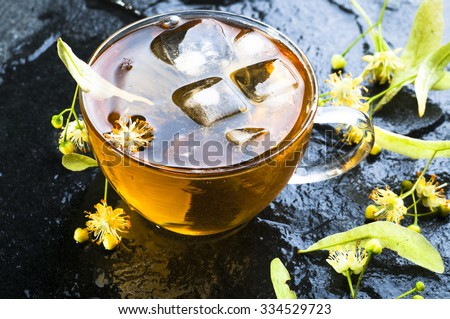 Herbal medicine series: Linden tea with ice cubes in cup  and flowers on black stone background